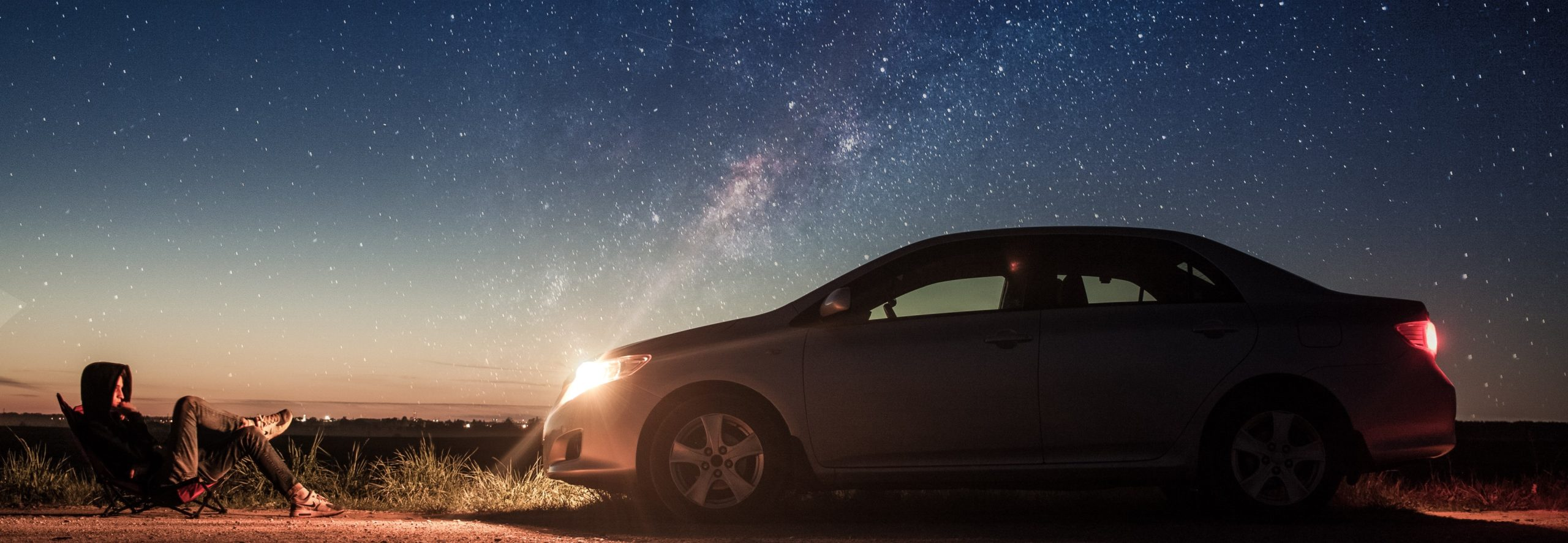 night sky, car with lights on - Joyride Car Rental